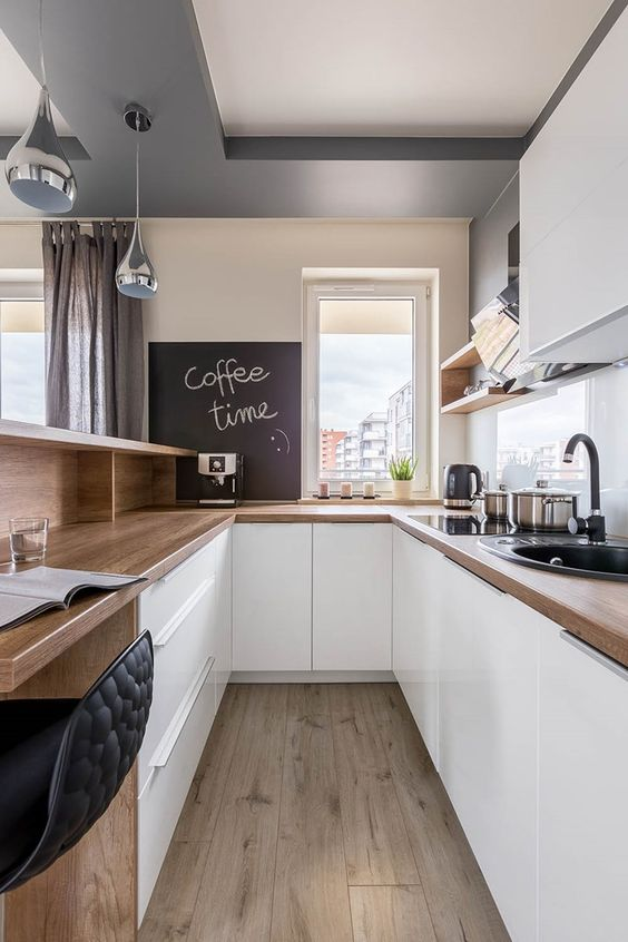 un'elegante cucina moderna bianca con controsoffitti butcherblock, scaffali aperti e armadietti e un bancone bar e uno spazio di lavoro in uno