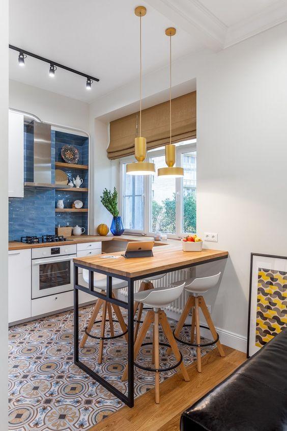 una piccola cucina contemporanea con armadi bianchi, piastrelle stampate sul pavimento, ripiani in macelleria e un tavolo a parete