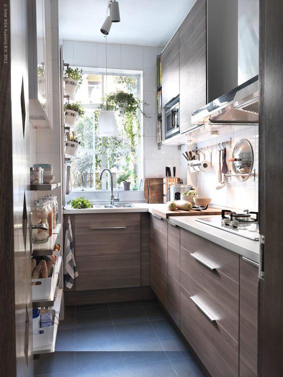 una piccola cucina marrone con ripiani bianchi e un paraschizzi bianco, lampade a sospensione e tocchi in acciaio inossidabile