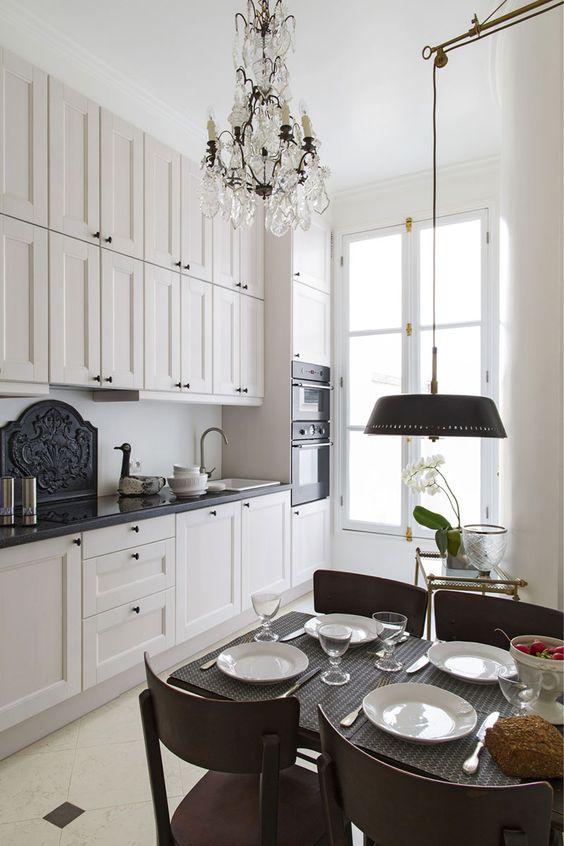 una piccola e chic cucina in stile francese con ripiani neri, lampadari di cristallo, una piccola zona pranzo con una lampada aggiuntiva