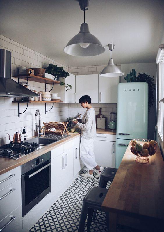 una piccola e accogliente cucina scandinava con armadi bianchi, controsoffitti butcherblock, un frigorifero alla menta e un backsplash di piastrelle bianche