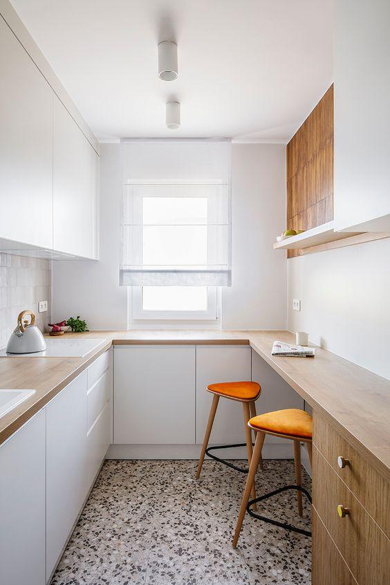 una piccola cucina minimalista con eleganti mobili bianchi, controsoffitti butcherblock e un bancone bar per cucinare e mangiare