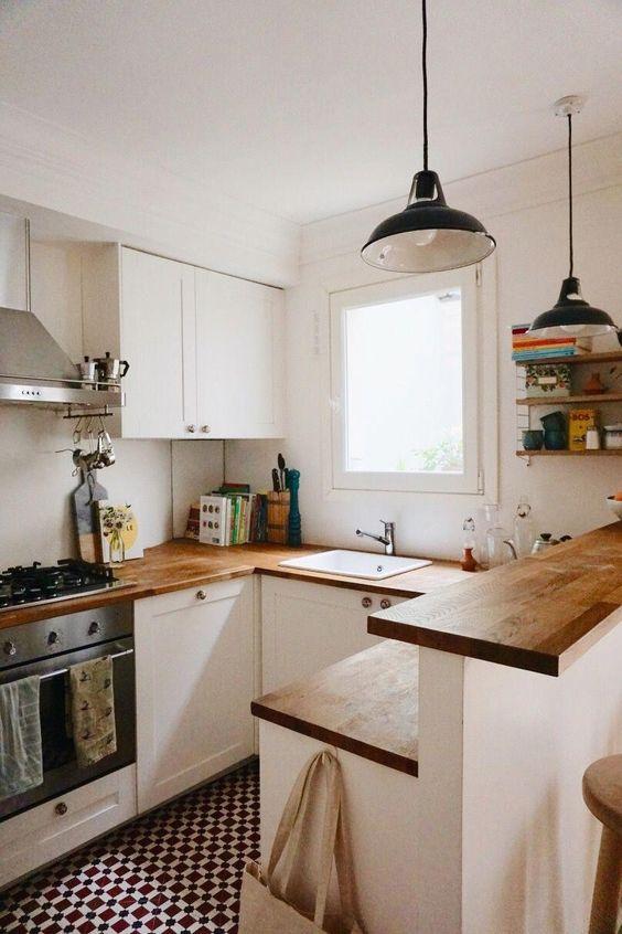 una piccola cucina moderna bianca con controsoffitti butcherblock un'isola cucina con due piani, lampade a sospensione retrò