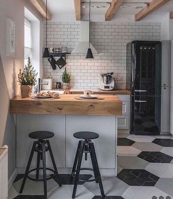 una piccola cucina scandinava in nero, bianco e grigio, con controsoffitti butcherblock e un backsplash di piastrelle bianche e lampade a sospensione