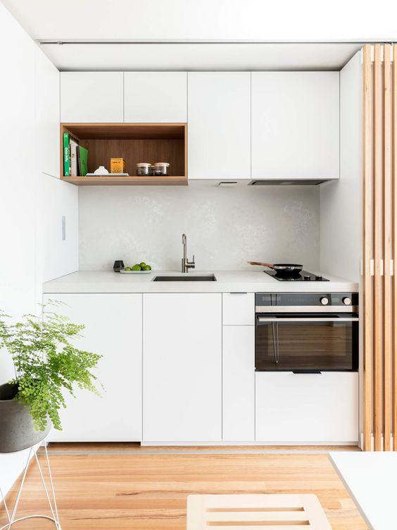 una piccola cucina minimalista in bianco, con un paraschizzi in piastrelle bianche e un piano di lavoro in pietra bianca che può essere nascosto con uno schermo