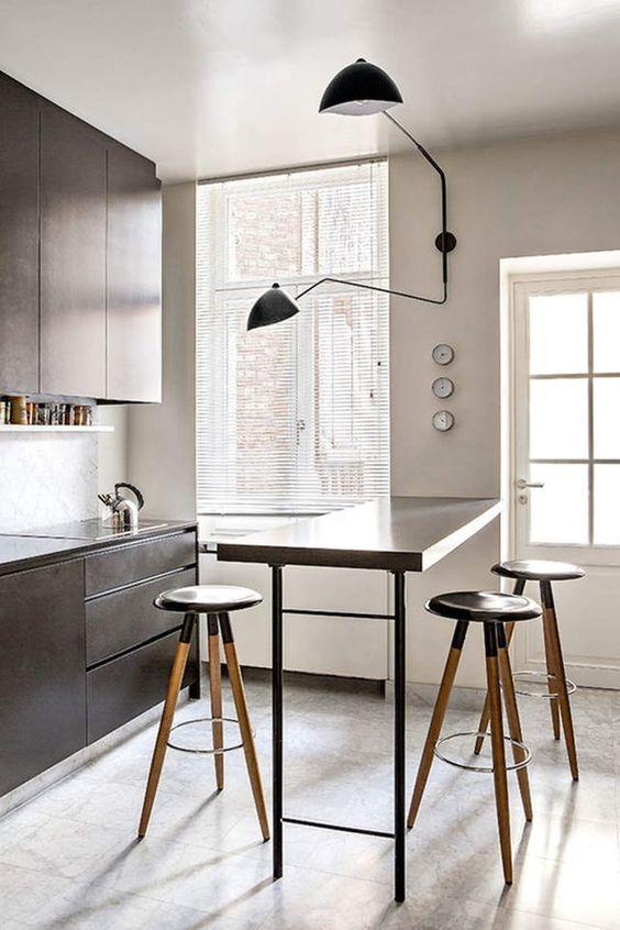 una piccola cucina con eleganti mobili marroni, un bancone bar alto e sgabelli alti più una bella applique