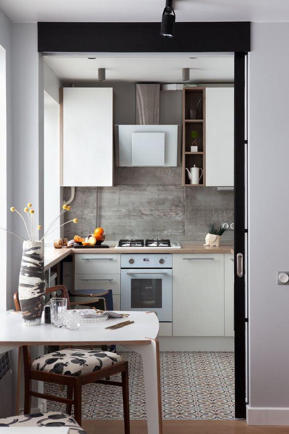 una piccola cucina moderna con piani di lavoro in muratura, un paraschizzi in cemento e un tavolino e sedie