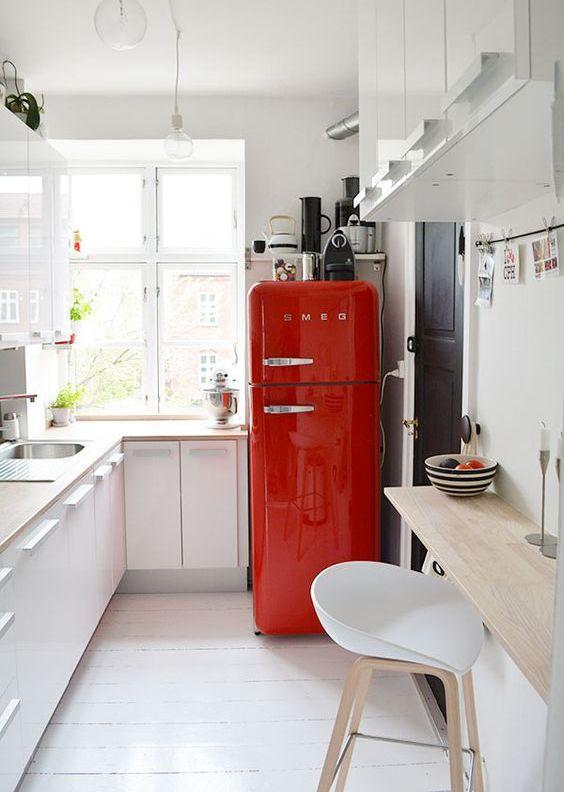 una piccola cucina bianca in stile scandinavo, ripiani in legno biondo, un frigorifero rosso audace per un tocco di colore