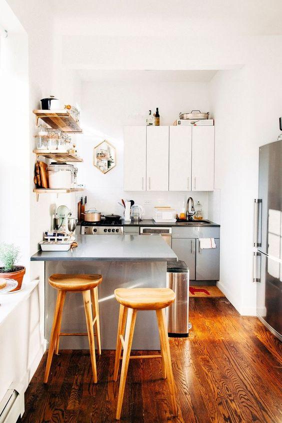una piccola cucina bicolore in grigio e bianco, con ripiani neri, scaffali aperti, sgabelli alti in legno e piante in vaso