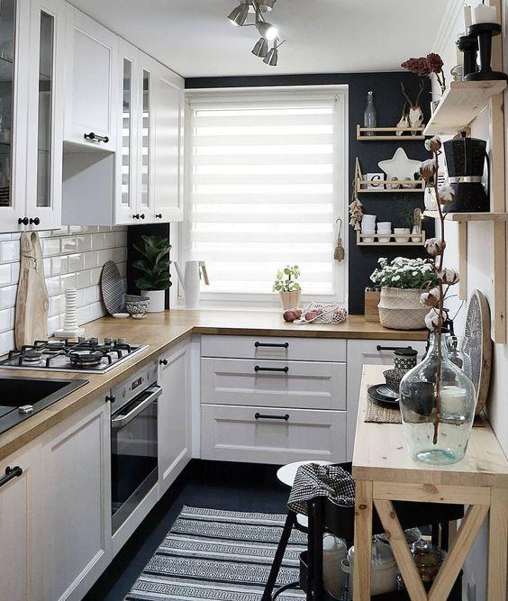 una piccola cucina scandinava con un paraschizzi di piastrelle bianche, controsoffitti butcherblock, scaffali aperti e pareti nere