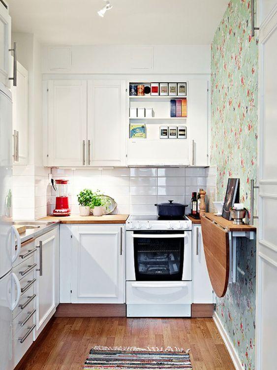 una piccola cucina bianca con un paraschizzi di piastrelle bianche sottili, una parete di carta da parati floreale, un tavolo pieghevole e un tappeto stampato