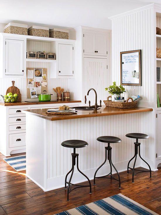 una piccola cucina da fattoria bianca con ripiani in legno tinto, sgabelli neri, scatole e cestini è accogliente