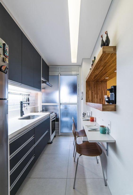 una piccola cucina nera lucida con uno spesso piano di lavoro in pietra bianca, un paraschizzi in piastrelle bianche, una mensola incorporata con una macchina per il caffè e un tavolo da bar