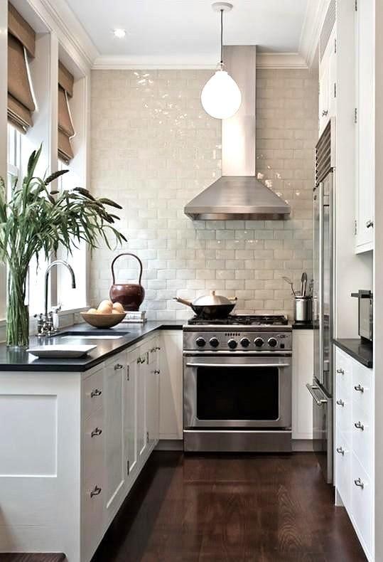 una piccola cucina bianca con ripiani neri, un paraschizzi in piastrelle smaltate bianche, sfumature, verde in un vaso e lampade a sospensione