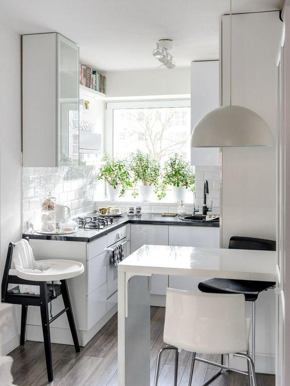 una piccola cucina scandinava con armadi bianchi lucidi, ripiani neri, bancone bar, lampada a sospensione e sgabelli