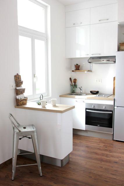 una piccola cucina bianca con controsoffitti butcherblock, un bancone bar che funge da isola cucina