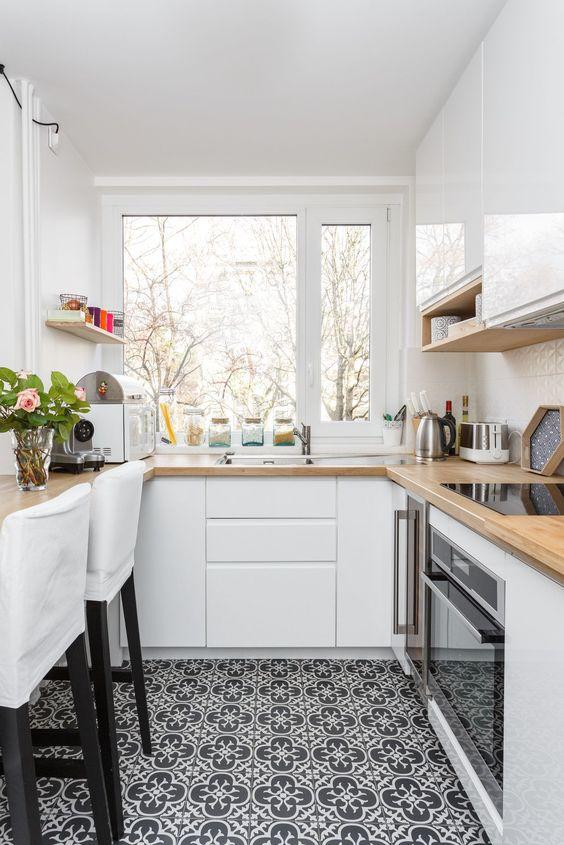una piccola cucina bianca con ripiani in macelleria, sgabelli bianchi e una finestra con vista