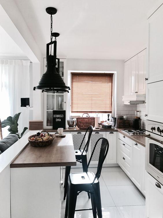 una piccola cucina bianca con controsoffitti macchiati scuri, piastrelle bianche sul paraschizzi, lampade a sospensione scure e sgabelli neri