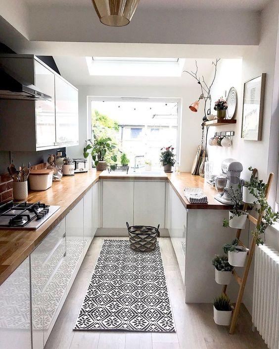 una piccola cucina bianca con controsoffitti butcherblock, piante in vaso, un tappeto stampato e lampade a sospensione