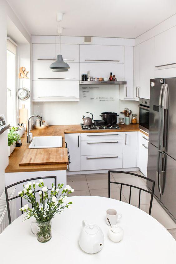 una piccola cucina bianca con controsoffitti butcherblock, maniglie neutre e lampade a sospensione più una zona pranzo