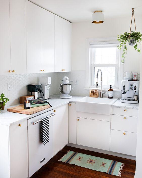una piccola cucina bianca con piastrelle in penny, con ripiani in pietra bianca, pomelli dorati e piante in vaso