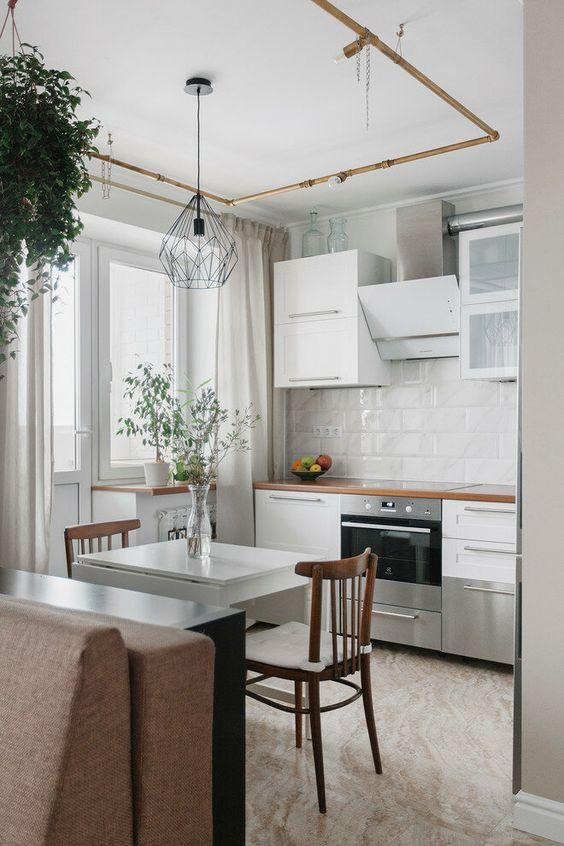una piccola cucina bianca con ripiani macchiati, un paraschizzi in piastrelle bianche, un mini tavolo e sedie pieghevoli