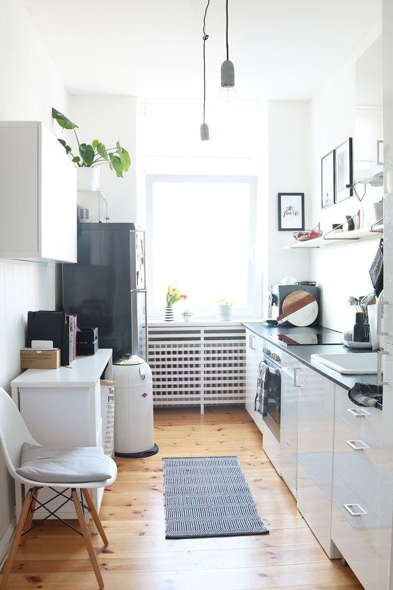 un'elegante cucina scandinava con ripiani neri, frigorifero nero, scaffali aperti e una mini cucina a isola