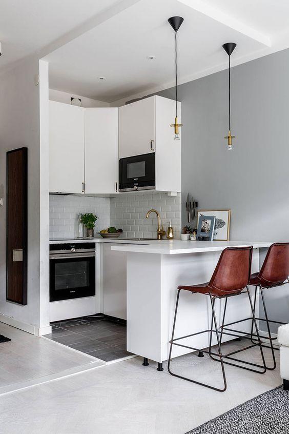 una piccola cucina bianca con piastrelle bianche, lampade a sospensione, sgabelli in pelle marrone e tocchi dorati è chic