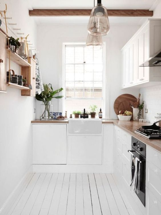 una piccola cucina scandinava bianca con ripiani in macelleria, una mensola in legno tinto e travi in legno sul soffitto