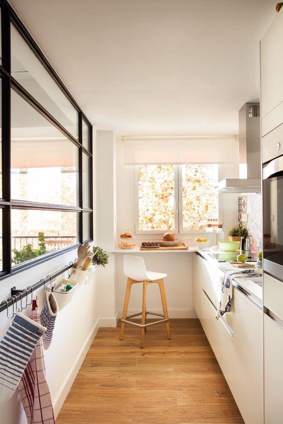 una piccola ma accogliente cucina bianca minimalista con piani di lavoro neutri, una grande finestra, un supporto per gli asciugamani e un davanzale