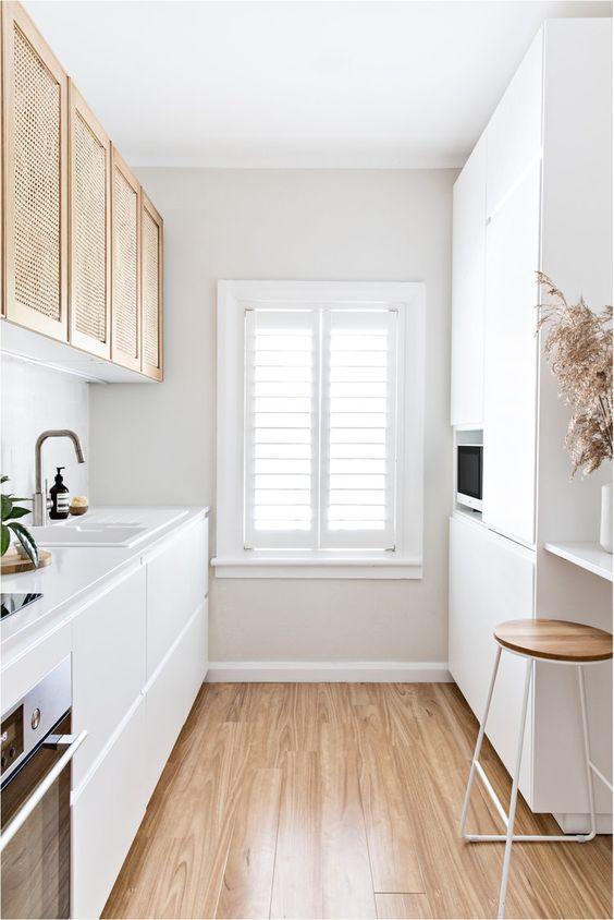 una piccola cucina bianca con mobili eleganti e canneti, con elettrodomestici da incasso e un bancone bar