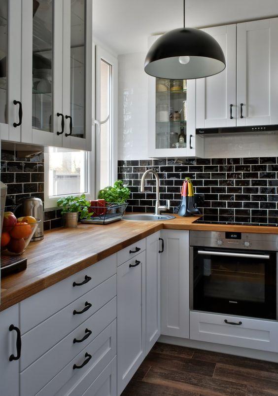 una cucina da fattoria bianca con piastrelle smaltate nere, controsoffitti butcherblock, lampade a sospensione nere