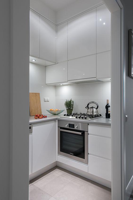 una piccola cucina bianca elegante con luci integrate, ripiani in metallo, elettrodomestici da incasso è chic e cool