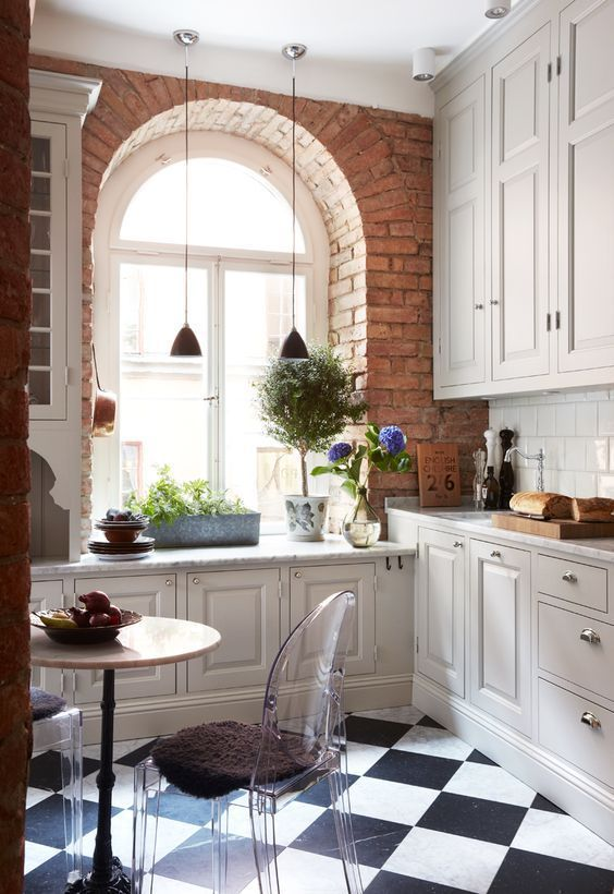una cucina da fattoria bianca con un davanzale e piante in vaso, un tavolo rotondo, sedie fantasma e un paraschizzi in piastrelle bianche