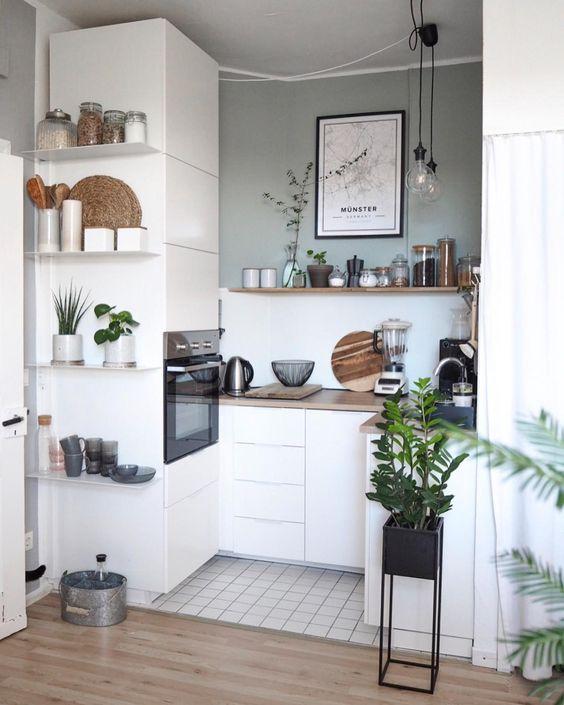 una minuscola cucina scandinava con eleganti armadi bianchi, alcuni scaffali aperti ed elettrodomestici da incasso oltre a lampade a sospensione