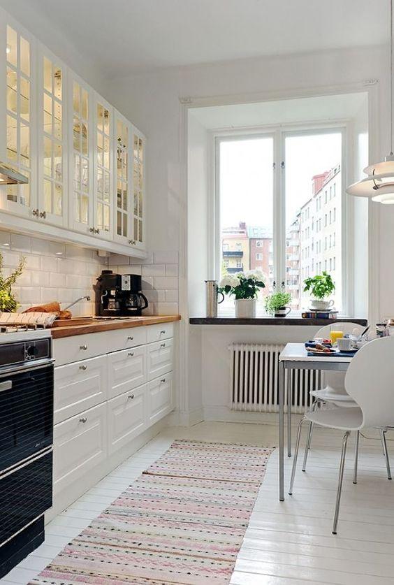 un'accogliente cucina scandinava bianca con pensili in vetro, piastrelle bianche, piani di lavoro in macelleria e una piccola zona pranzo