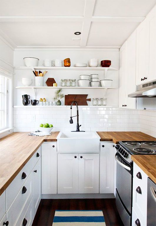 una cucina da fattoria bianca con controsoffitti butcherblock, scaffali aperti e maniglie e pomelli neri
