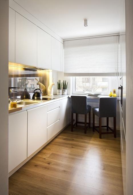 una cucina minimalista bianca con un paraschizzi lucido, luci integrate, un bancone per la colazione sul davanzale della finestra