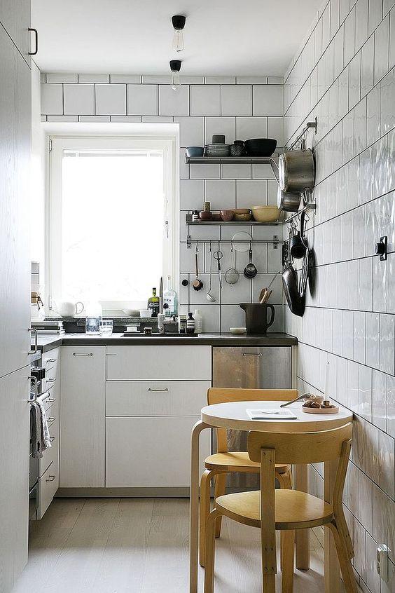 una cucina moderna bianca completamente rivestita di piastrelle, ripiani neri, un tavolo rotondo e sgabelli è comoda