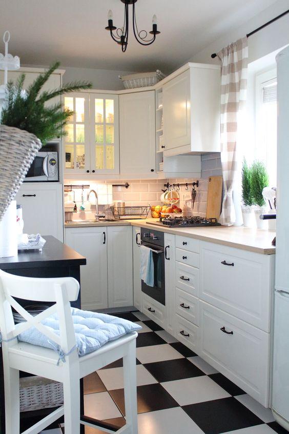 una cucina rustica bianca con un pavimento a quadri, piani di lavoro in macelleria e sgabelli alti e lampadari vintage