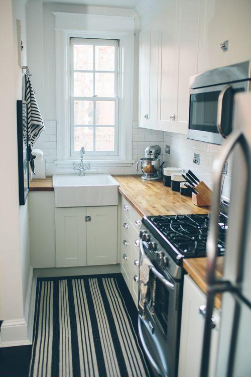 una cucina moderna bianca con controsoffitti butcherblock, un backsplash di piastrelle bianche, un tappeto a righe e maniglie neutre