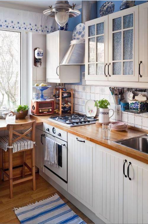 una cucina da fattoria bianca con controsoffitti butcherblock, sgabelli alti e tocchi blu per l'intimità