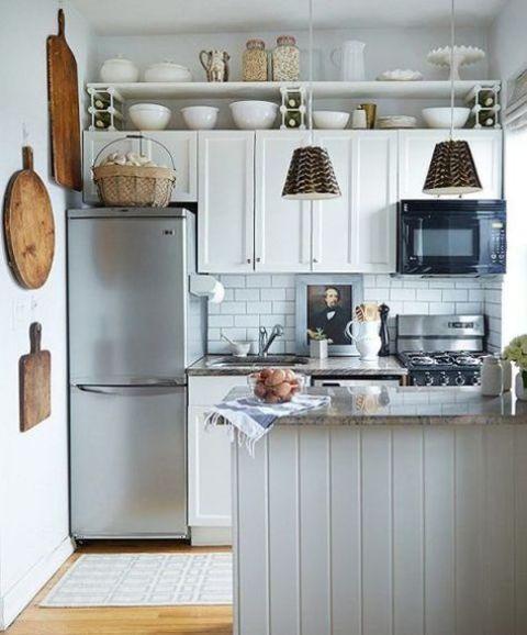 una cucina da fattoria bianca con piastrelle della metropolitana, un'isola da cucina e lampade a sospensione e tocchi di legno