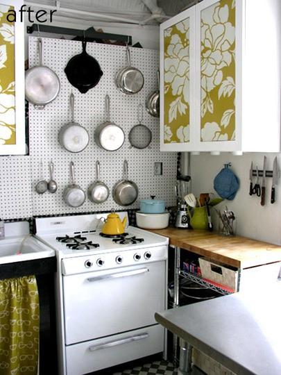 una piccola cucina moderna con armadietti stampati floreali, un pannello forato per tenere pentole, un fornello e controsoffitti butcherblock