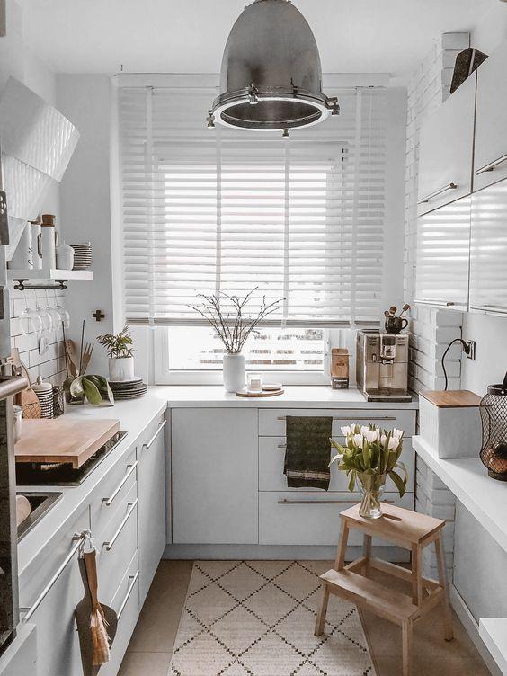 una cucina scandinava bianca con ripiani bianchi, lampade a sospensione e tocchi di legno qua e là