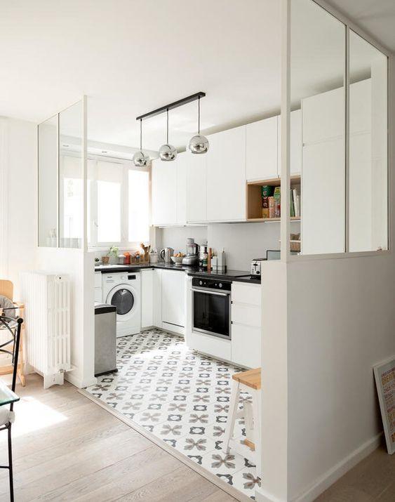una cucina bianca elegante con un paraschizzi bianco, piani di lavoro neri e lampade metalliche oltre a un pavimento piastrellato stampato