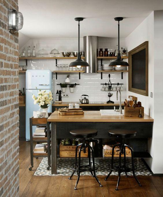 una cucina industriale con mobili neri, controsoffitti butcherblock, un paraschizzi in piastrelle bianche e lampade a sospensione