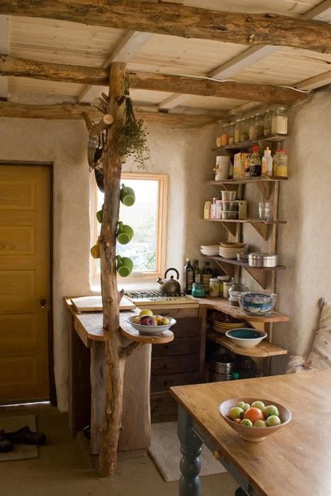 una piccola cucina wabi-sabi con ripiani a giorno, travi in legno grezzo sul soffitto e un pilastro porta tazze, un tavolo aggiuntivo che può essere utilizzato come isola cucina