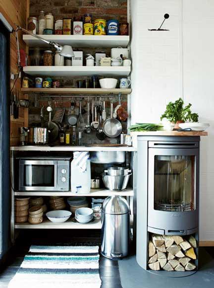 un minuscolo angolo cottura con ripiani aperti, un piccolo piano cottura, un forno a microonde e accanto una stufa a legna usata anche come piano di lavoro