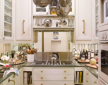 un'elegante cucina neutra con pomelli e maniglie dorate, con ripiani scuri e massima funzionalità, ogni centimetro è preso